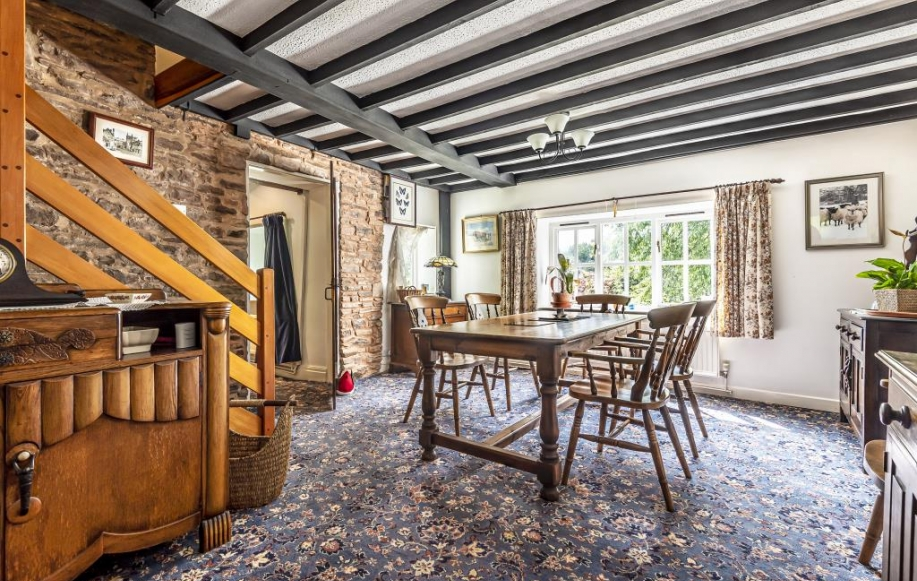 Dining room with ceiling beams & views of garden